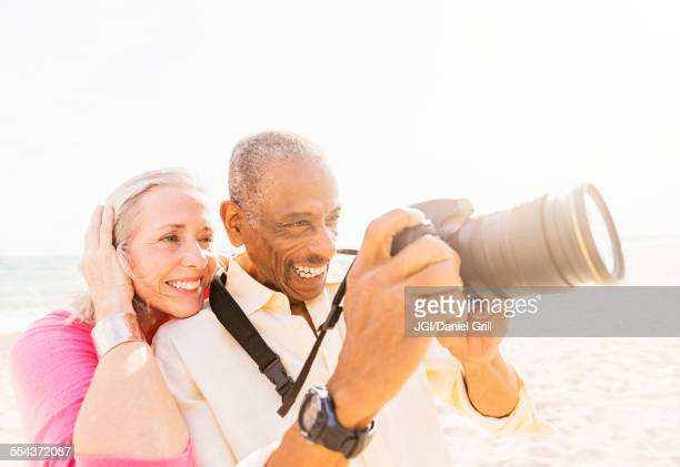 Older couple photographing on beach