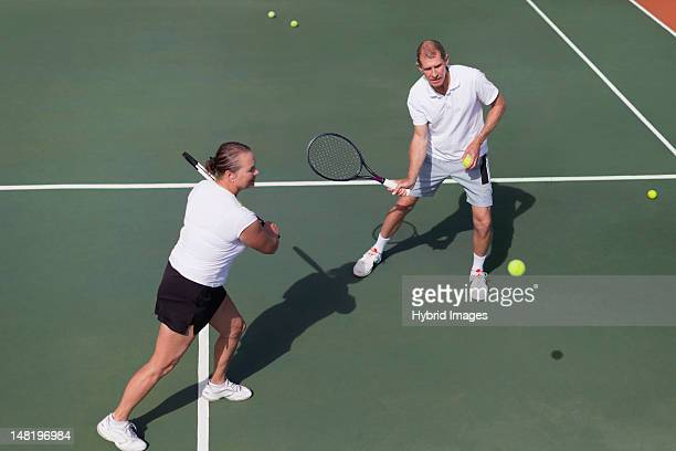 Older couple playing tennis on court