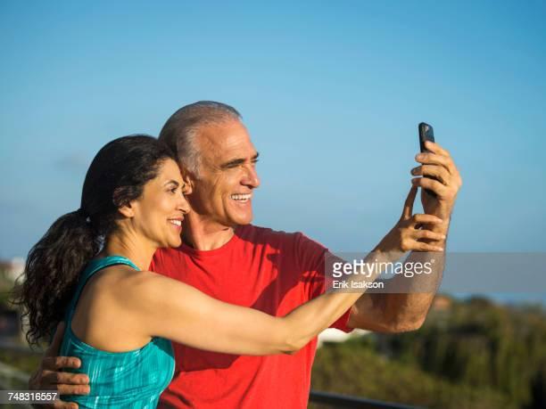 Older couple posing for cell phone selfie
