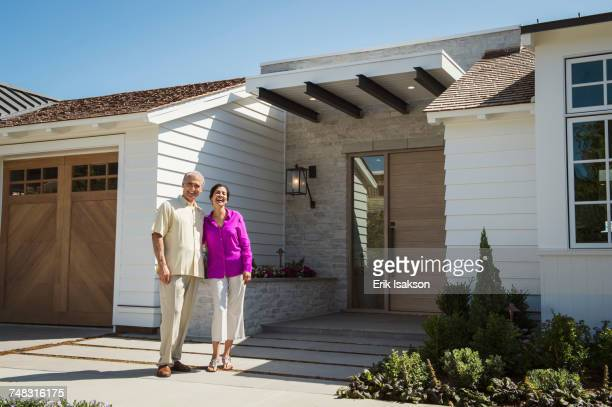 Older couple posing near driveway of house