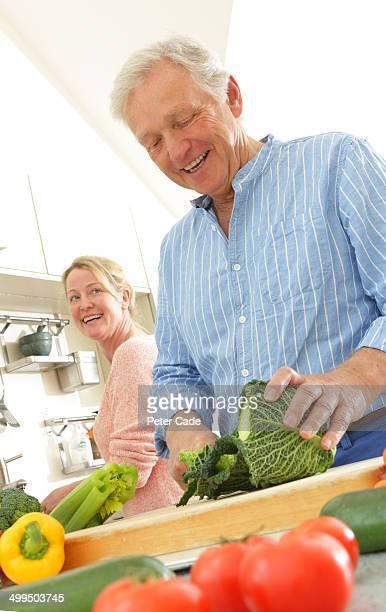 Older couple preparing food in kitchen