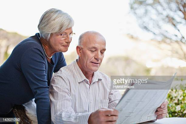 older couple reading newspaper outdoors - 50 59 years stock pictures, royalty-free photos & images