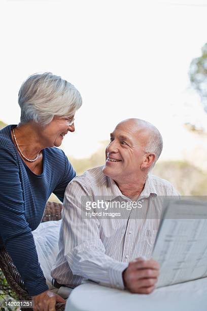Older couple reading newspaper outdoors