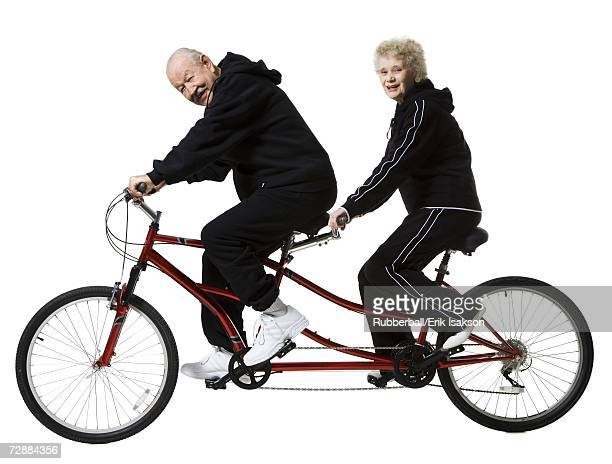older couple riding a tandem bicycle - tandem bicycle stock pictures, royalty-free photos & images
