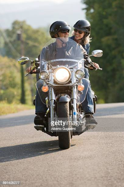 Older couple riding motorcycle on empty road