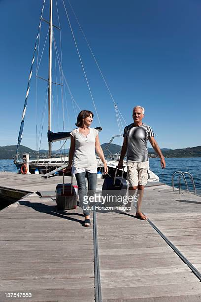 Older couple rolling luggage on pier