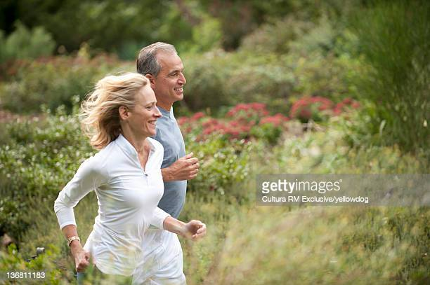 Older couple running in park
