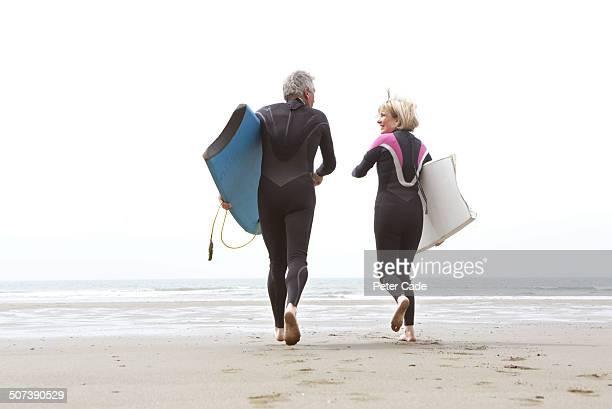 Older couple running into sea wih bodyboards
