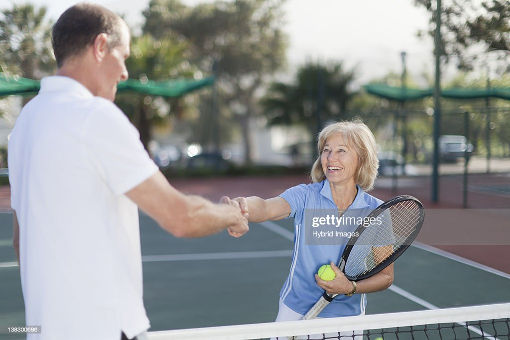 Older couple shaking hands on court : Stock Photo