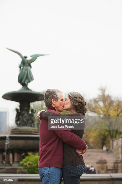 Older couple sharing a kiss by the fountain