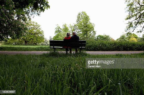older couple sitting on park bench - bench stock pictures, royalty-free photos & images