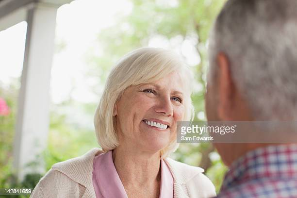 Older couple smiling at each other outdoors