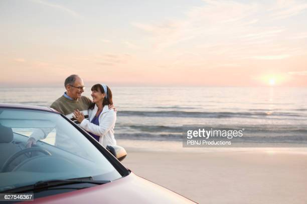 Older couple standing at car on beach
