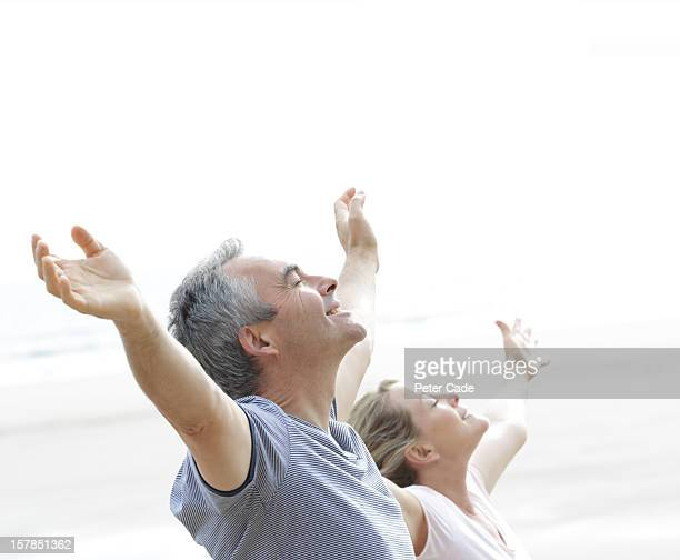Older couple stretching arms i air