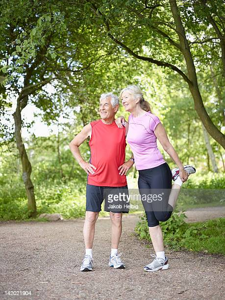 Older couple stretching in park