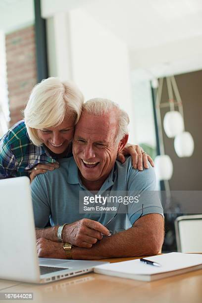 older couple using laptop together - boyfriend stock pictures, royalty-free photos & images