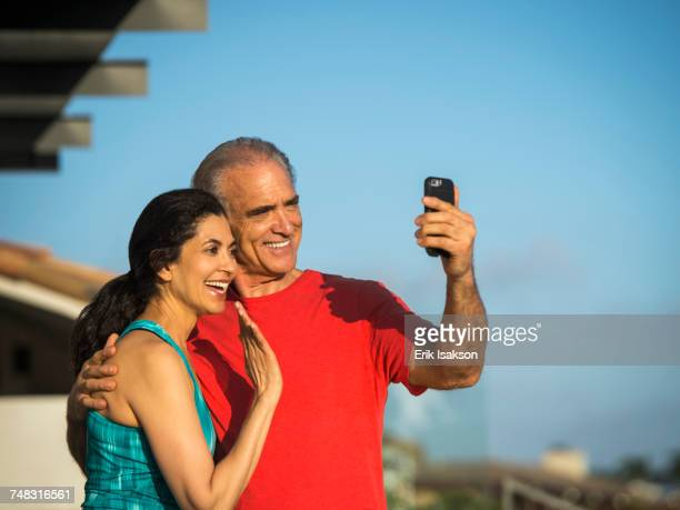 Older couple waving and posing for cell phone selfie