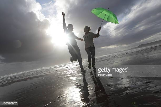 Older couple with umbrella having fun on beach