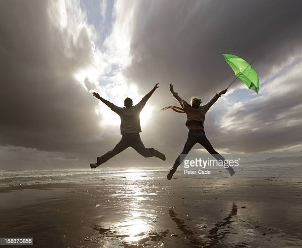 older couple with umbrella jumping on beach - legs apart stock pictures, royalty-free photos & images