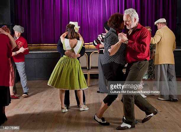 Older couples dancing in auditorium