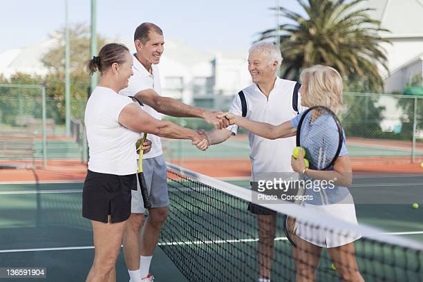 older couples shaking hands at tennis - doubles stock photos and pictures