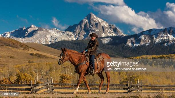 Older Cowboy, Howard Linscott , leads packhorse across historic Last Dollar Ranch on Hastings Mesa, SW Colorado, San Juan Mountains.