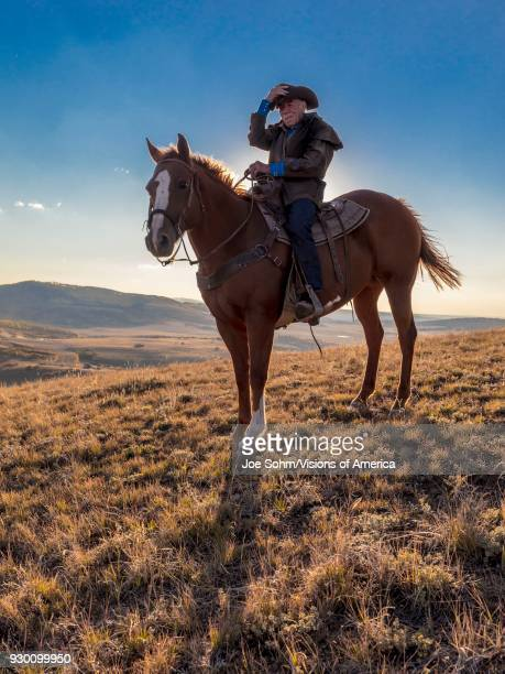 Older Cowboy, Howard Linscott looks out over historic Last Dollar Ranch on Hastings Mesa, SW Colorado, San Juan Mountains.