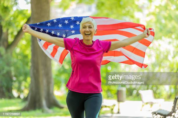 older female american patriot with the usa flag - patriotism stock pictures, royalty-free photos & images