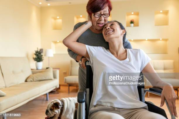 older female physiotherapist is giving a treatment to a mature woman in a wheelchair at home. - chinese bulldog stock pictures, royalty-free photos & images