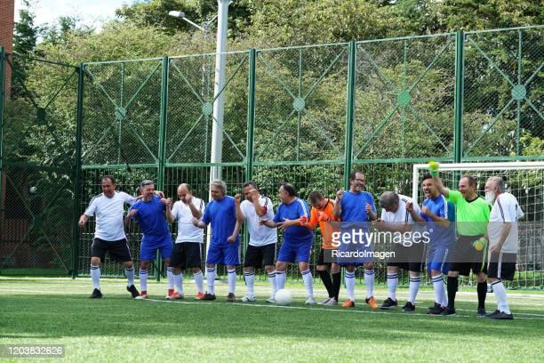 oudere voetballers van het blauw-witte team met hun respectievelijke keepers worden afgewisseld voor een foto voordat ze beginnen met het spel allemaal op het veld - verdediger voetballer stockfoto's en -beelden