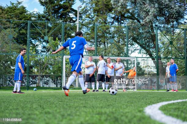 older footballer will charge a free kick to place his team forward on the scoreboard - soccer competition stock pictures, royalty-free photos & images