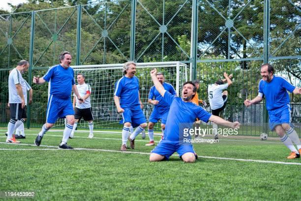 footballeurs plus âgés célébrant un but marqué par l'équipe rivale - marquer un but photos et images de collection