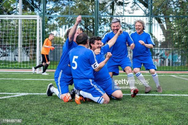 footballeurs plus âgés célébrant un but marqué par l'équipe rivale - club football photos et images de collection