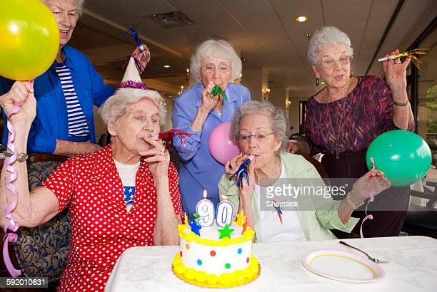 Older friends celebrating birthday in retirement home