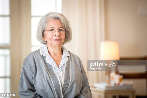 older frowning hispanic woman wearing bathrobe - frowning stock pictures, royalty-free photos & images