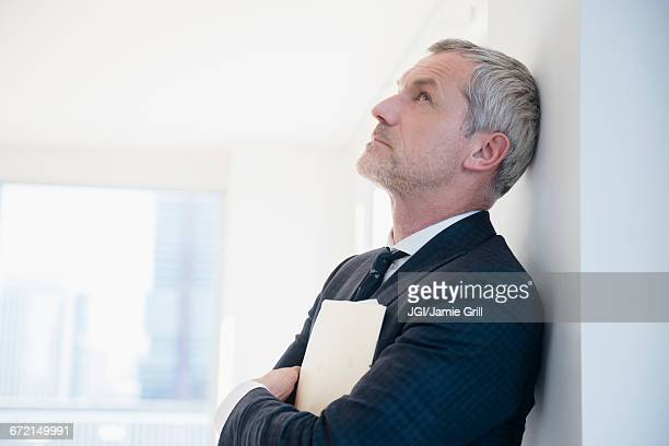 Older frustrated Caucasian businessman leaning on wall