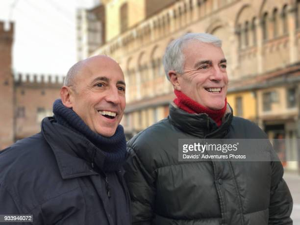 older gay couple holding hands and walking in historic european piazza - gay seniors photos et images de collection