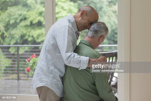 Older gay male comforting his senior gay husband