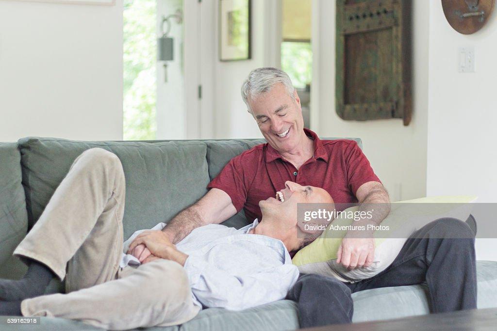 Older Gay Male Couple Affectionately On Sofa Stock Photo
