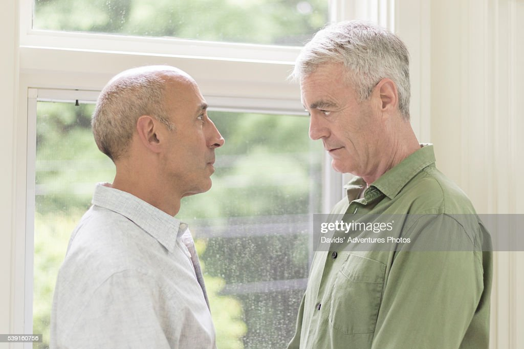 Older Gay Male Couple Having Serious Discussion Stock Photo