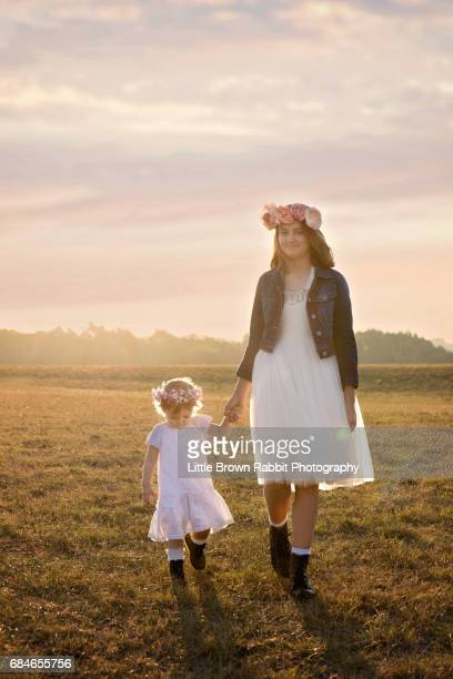 Older Girl And Younger Sister In A Field At Sunset