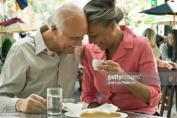 Older Hispanic couple having breakfast at sidewalk cafe
