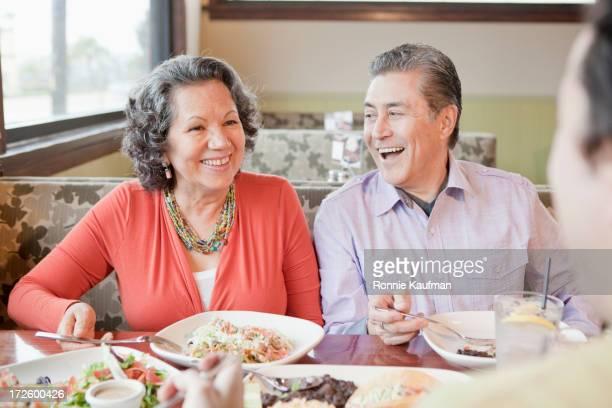 Older Hispanic couple having dinner in restaurant