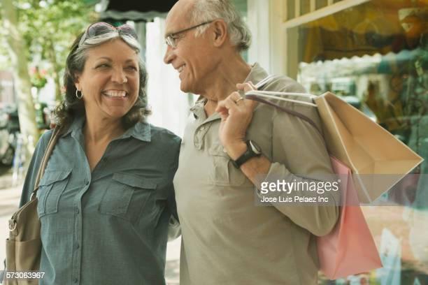 Older Hispanic couple shopping on urban sidewalk