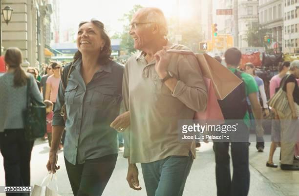 Older Hispanic couple walking on urban sidewalk