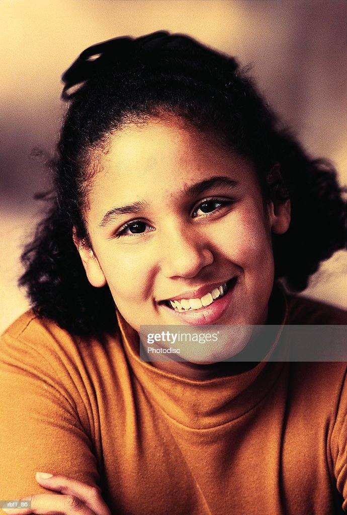 older hispanic girl with dark hair half pulled up wearing an orange turtleneck tilts her head and smiles with her arms folded in front of her : Stockfoto