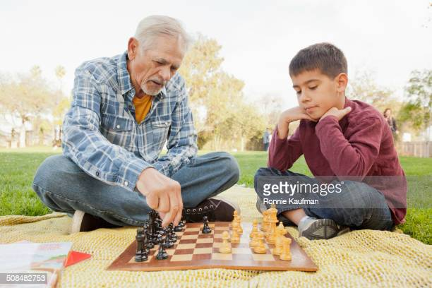 Older Hispanic man and grandson playing chess in park