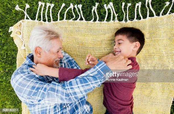 older hispanic man and grandson playing in park - rough housing stock pictures, royalty-free photos & images