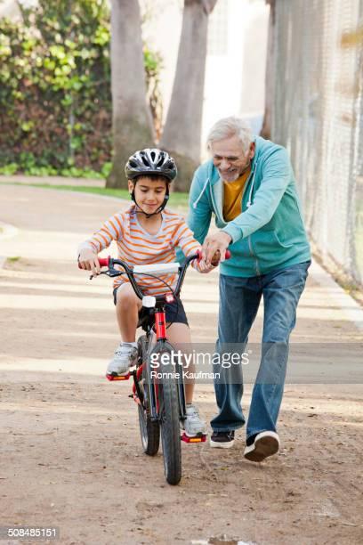 Older Hispanic man teaching grandson to ride bicycle