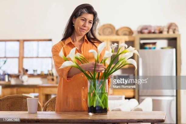 Older Hispanic woman arranging flowers in kitchen